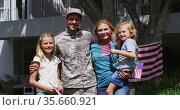 Portrait of caucasian military man in uniform and his family smiling in the garden. Стоковое видео, агентство Wavebreak Media / Фотобанк Лори