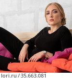 Beautiful woman in black suit posing on low sofa. Стоковое фото, фотограф Гурьянов Андрей / Фотобанк Лори