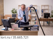 Old businessman employee holding vacuum cleaner at workplace. Стоковое фото, фотограф Elnur / Фотобанк Лори