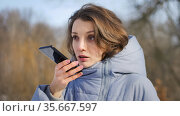 Young girl in blue coat is using her smartphone to send a voice message to a new social network Clubhouse standing somewhere outdoors at the park, focus on the phone. Стоковое фото, фотограф Ольга Балынская / Фотобанк Лори