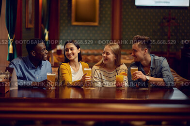 Four friends drinks alcohol at the counter in bar