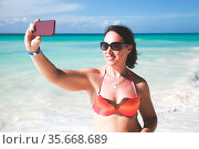 Pretty woman in sunglasses takes selfie photo on the beach. Стоковое фото, фотограф EugeneSergeev / Фотобанк Лори