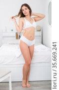Flirtatious girl in white lingerie standing near bed. Стоковое фото, фотограф Яков Филимонов / Фотобанк Лори