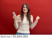 Angry Young beautiful caucasian girl wearing beige jacket and jeans over red background screaming on phone. Стоковое фото, фотограф Дарья Филимонова / Фотобанк Лори