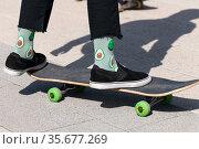 legs of teenager in green socks on a skateboard. Стоковое фото, фотограф Володина Ольга / Фотобанк Лори