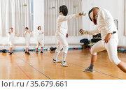 Adults and teens wearing fencing uniform practicing with foil. Стоковое фото, фотограф Яков Филимонов / Фотобанк Лори