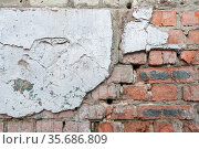 Weathered red brick wall for texture or background, rough aged brickwork, masonry with remnants peeling cement plaster. Стоковое фото, фотограф Андрей Копылов / Фотобанк Лори
