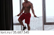 Athletic shirtless man jumping over the rope in the studio with panoramic windows. Стоковое видео, видеограф Константин Шишкин / Фотобанк Лори