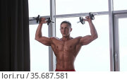 Athletic muscular shirtless man training his hands muscles with the dumbbells. Стоковое видео, видеограф Константин Шишкин / Фотобанк Лори