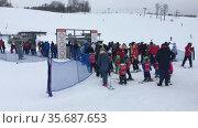 Взрослые и дети стоят в очереди на горнолыжный подъемник в парке Туутари. Редакционное видео, видеограф Кекяляйнен Андрей / Фотобанк Лори