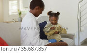 African american girl using stethoscope and smiling during medical home visit. Стоковое видео, агентство Wavebreak Media / Фотобанк Лори