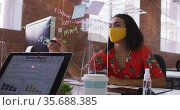 Mixed race businesswoman writing on sneez screen sitting in front of computer wearing face mask. Стоковое видео, агентство Wavebreak Media / Фотобанк Лори