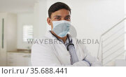 Portrait of hispanic male doctor at home, all wearing face mask. Стоковое видео, агентство Wavebreak Media / Фотобанк Лори