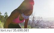 Tired african american woman wearing face mask taking a break from running outdoors. Стоковое видео, агентство Wavebreak Media / Фотобанк Лори
