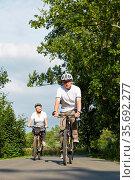 Frau und Mann fahren Fahrrad mit Helm im Sommer. Стоковое фото, фотограф Zoonar.com/Robert Kneschke / age Fotostock / Фотобанк Лори