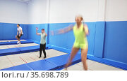 Group of active friends practicing and jumping in trampoline center. Стоковое видео, видеограф Яков Филимонов / Фотобанк Лори