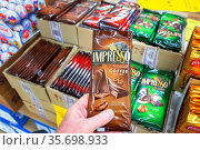 Russia, Samara, February 2021: a man's hand holds a chocolate bar in his hand, chooses a gift for children. Редакционное фото, фотограф Акиньшин Владимир / Фотобанк Лори