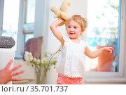 Blondes Mädchen wirft ihr Kuscheltier zum Vater zu Hause. Стоковое фото, фотограф Zoonar.com/Robert Kneschke / age Fotostock / Фотобанк Лори