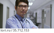 Portrait of asian male doctor with arms crossed smiling while standing in the corridor at hospital. Стоковое видео, агентство Wavebreak Media / Фотобанк Лори