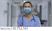 Portrait of caucasian female health worker wearing face mask in the corridor at hospital. Стоковое видео, агентство Wavebreak Media / Фотобанк Лори
