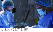 Diverse surgeons wearing surgical caps and face masks in operating theatre in hospital. Стоковое видео, агентство Wavebreak Media / Фотобанк Лори