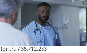 Smiling african american male doctor discussing with diverse colleagues at a hospital staff meeting. Стоковое видео, агентство Wavebreak Media / Фотобанк Лори