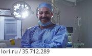 Portrait of caucasian male surgeon wearing lowered face mask smiling in operating theatre. Стоковое видео, агентство Wavebreak Media / Фотобанк Лори