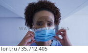Portrait of mixed race female doctor putting face mask on. Стоковое видео, агентство Wavebreak Media / Фотобанк Лори