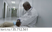 Tired african american male doctor sitting on hospital corridor holding face mask. Стоковое видео, агентство Wavebreak Media / Фотобанк Лори