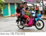 Familienfahrt mit Regenschirm auf einer Fahrt mit dem Moped im Regen... Стоковое фото, фотограф Zoonar.com/Georg_A / age Fotostock / Фотобанк Лори