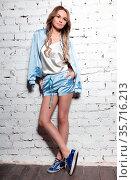 Cute young lady posing in studio dressed in sportswear, t-shirt and... Стоковое фото, фотограф Zoonar.com/Sergey Sukhorukov / easy Fotostock / Фотобанк Лори