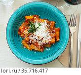 Italian pasta amatricana with tomato sauce and goat cheese on a blue ceramic plate in a restaurant. Стоковое фото, фотограф Яков Филимонов / Фотобанк Лори