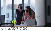 Two diverse female colleague wearing face masks standing at table looking at blueprints and talking. Стоковое видео, агентство Wavebreak Media / Фотобанк Лори