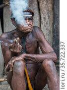 Dani tribe man smoking. Jiwika village, Suroba, Trikora Mountains, West Papua, Indonesia. October 2020. Стоковое фото, фотограф Pete Oxford / Nature Picture Library / Фотобанк Лори