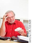 Besorgter Rentner schaut nachdenklich auf Euro-Geldscheine in seiner... Стоковое фото, фотограф Zoonar.com/Robert Kneschke / age Fotostock / Фотобанк Лори