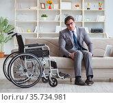Dsabled businessman on wheelchair working home. Стоковое фото, фотограф Elnur / Фотобанк Лори