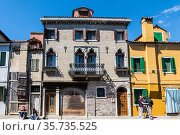 The facade of an old building with Venetian windows and a balcony with a metal decorative lattice on the bank of the canal. Burano Island, Venice, Italy (2017 год). Редакционное фото, фотограф Наталья Волкова / Фотобанк Лори