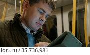 Man Using Tablet PC in Metro Train. Стоковое фото, фотограф Данил Руденко / Фотобанк Лори