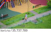 Moscow, Russia - July 15.2021. The janitor is sweeping the cut grass. cityscape. Редакционное видео, видеограф Володина Ольга / Фотобанк Лори