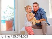 Vater und Tochter mit Kuscheltier zu Hause im Wohnzimmer. Стоковое фото, фотограф Zoonar.com/Robert Kneschke / age Fotostock / Фотобанк Лори