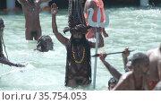 Kumbh Mela Haridwar India. Slowmotion shot of Sadhus or Saints of Akharas taking bath in Holy Water of River Ganges. Worship with Trishul and Shank ornament. Appleprores 422 Cinetone. Редакционное видео, видеограф Devendra Rawat / Фотобанк Лори