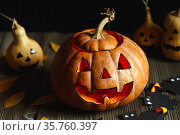 Halloween design with pumpkins. Horrible symbol of Halloween - Jack-o-lantern. Scary head of pumpkin with flame and a few small painted gourds. Glowing face, trick or treat. Copy Space. Стоковое фото, фотограф Nataliia Zhekova / Фотобанк Лори