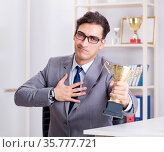 Businessman with prize cup for achievements in office. Стоковое фото, фотограф Elnur / Фотобанк Лори