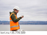 Geologist or mining engineer examines a sample of a mineral from a talus on a river bank. Стоковое фото, фотограф Евгений Харитонов / Фотобанк Лори