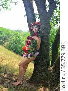 Girl in a dress of flowers near a tree. Стоковое фото, фотограф Арестов Андрей Павлович / Фотобанк Лори