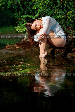 Attractive girl in lingerie and white shirt is sitting on a rock by...
