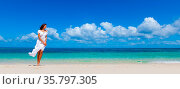 Woman in white dress walking in tropical sea beach enjoying wind. Стоковое фото, фотограф Zoonar.com/Ivan Mikhaylov / easy Fotostock / Фотобанк Лори