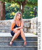 Young woman is sitting on staircase in park looking at camera slight... Стоковое фото, фотограф Emil Pozar / age Fotostock / Фотобанк Лори