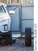 Suv standing on jack-screw for snow tire removing, summer wheel is ready to install. Стоковое фото, фотограф Кекяляйнен Андрей / Фотобанк Лори