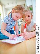 Zwei Mädchen malen Bild zusammen mit Filzstiften zu Hause. Стоковое фото, фотограф Zoonar.com/Robert Kneschke / age Fotostock / Фотобанк Лори